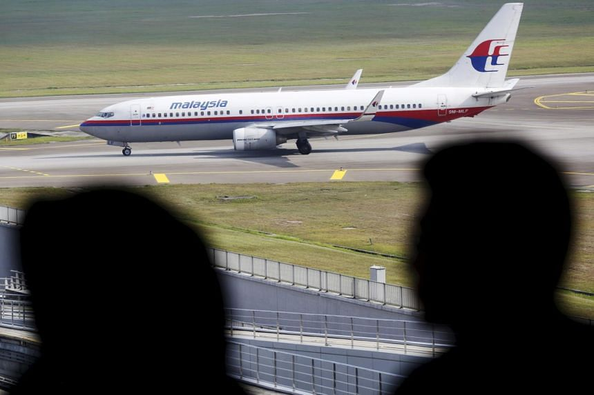 Men watch Malaysia Airlines aircraft at Kuala Lumpur International Airport in Sepang, Malaysia, in this picture taken on March 2.