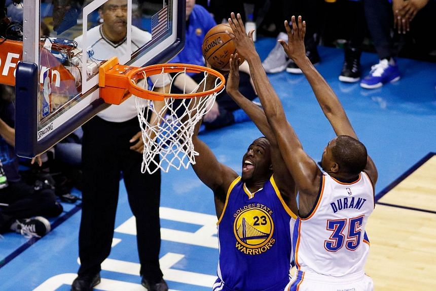 Draymond Green #23 of the Golden State Warriors shoots against Kevin Durant #35 of the Oklahoma City Thunder.