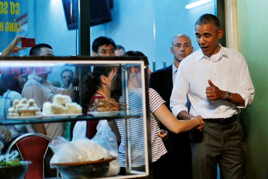Mr Obama flashes a thumbs-up after having dinner with Mr Bourdain at the local restaurant.