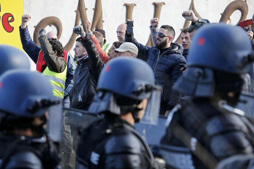 French gendarmes take position as striking workers blockade roads near a French oil refinery on May 24, 2016, over labour reforms.