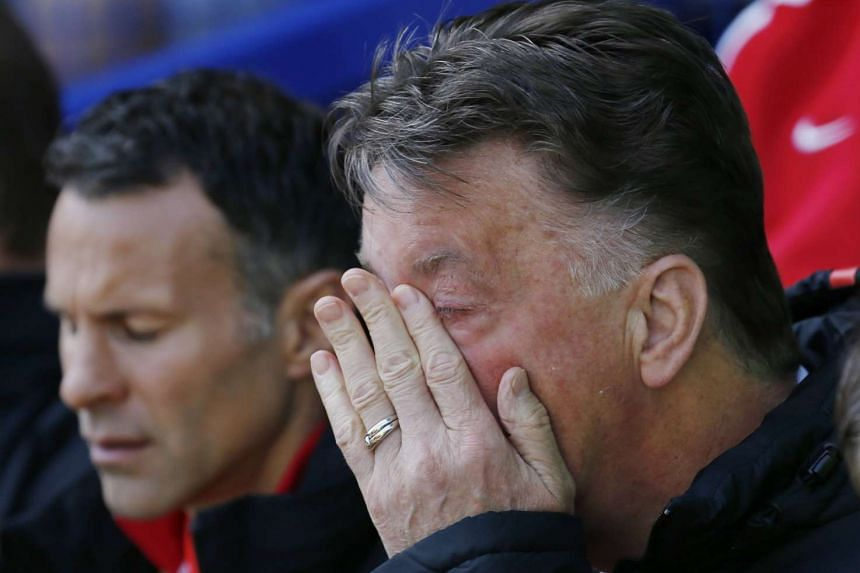 Manchester United manager Louis van Gaal covers his face with his hands as assistant manager Ryan Giggs looks downcast.