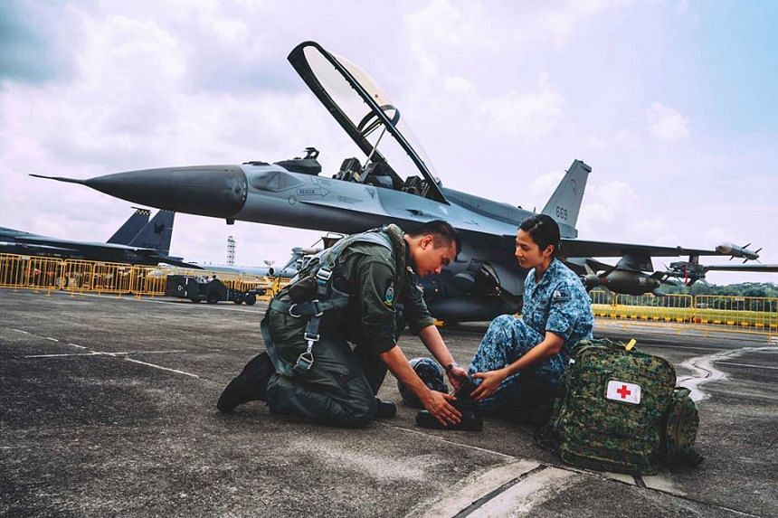 RSAF's own Captain Jonathan Lau (left) and Major (Dr) Magdalene Lee pose in uniform in front of a fighter jet at Paya Lebar Air Base.