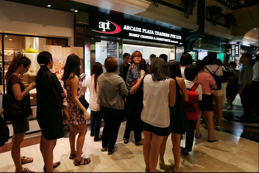 The queue at a moneychanger in Raffles Place when the ringgit hit a low last year.