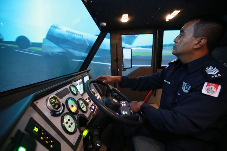Airport Emergency Services Officer Mohd Yazid, 46, demonstrating how the simulator is used to train workers who drive special vehicles called foam tenders, which use foam and water to put out fires at the airport.