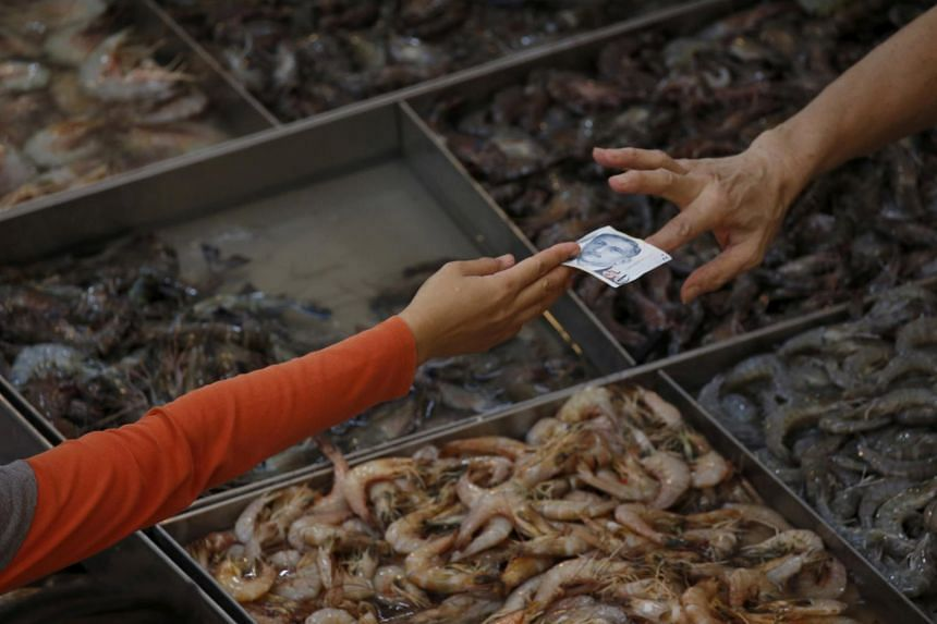 A customer pays for shrimp at a wet market in Singapore on March 23.