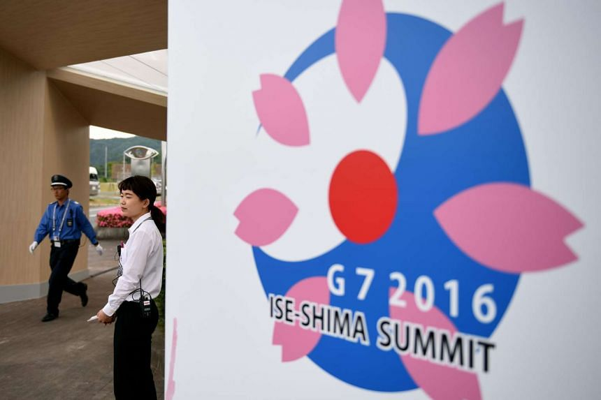 A 2016 Ise-Shima G7 Summit volunteer stands next to the summit's logo at the International Media Center in Ise-Shima on May 24, 2016. PHOTO: AFP