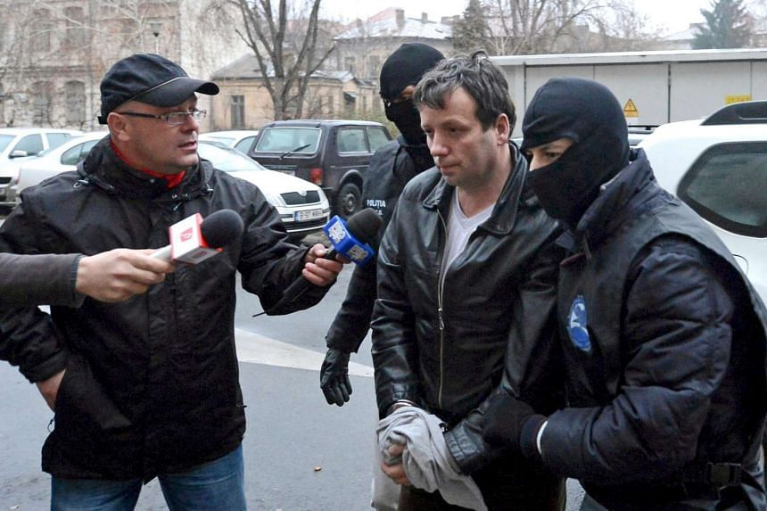 Marcel Lazar Lehel, 40, is escorted by masked policemen in Bucharest, after being arrested in Arad, 550 km west of Bucharest in this Jan 22, 2014 file picture.