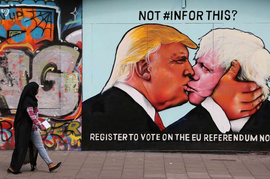 A passer-by views a mural showing likely US Republican presidential nominee Donald Trump (left) kissing the Former Mayor of London and Conservative MP, Boris Johnson, on the side of a building in Bristol, south west England on May 24, 2016.