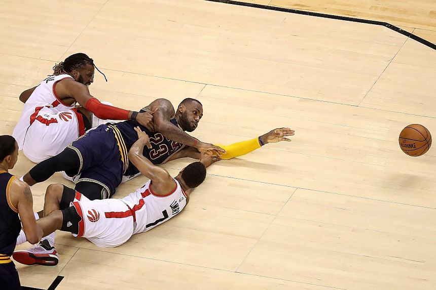 Ferocity on the floor as LeBron James (middle) of the Cleveland Cavaliers competes for the ball with DeMarre Carroll (left) and Kyle Lowry (No. 7) of the Toronto Raptors in Game 4 of the Eastern Conference Finals on Monday. The Raptors won 105-99 to