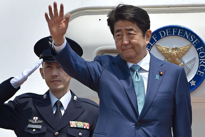 Japanese Prime Minister Shinzo Abe waves as he departs for major European countries at Tokyo's Haneda airport on May 1.