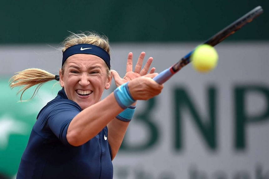 Azarenka returns the ball to Italy's Karin Knapp during their women's first round match.