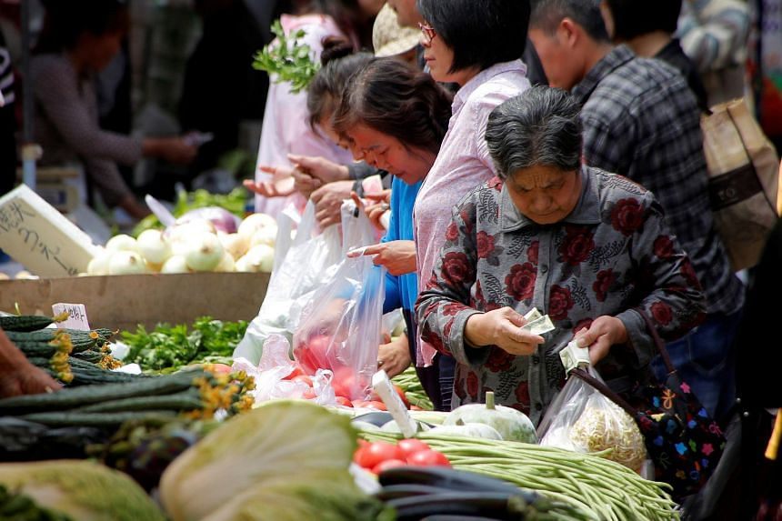 A customer counts her money as she purchases vegetables at a market in Beijing, China on May 9.