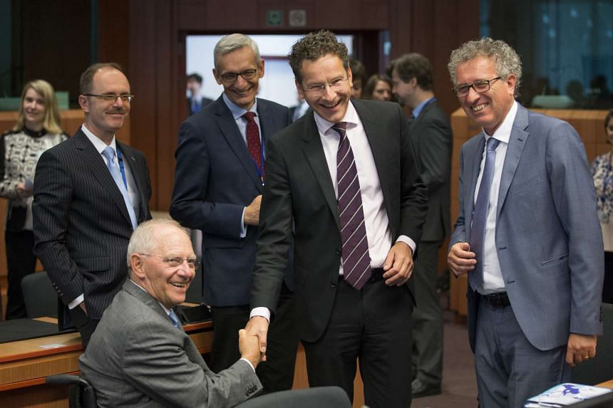 Dutch Finance Minister Jeroen Dijsselbloem (second from right) shakes hands with German Finance Minister Wolfgang Schauble.