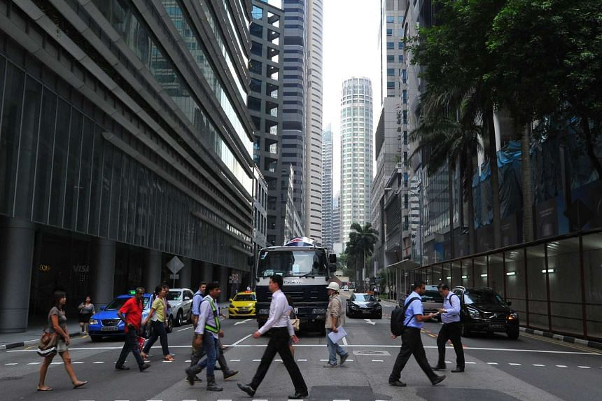People walk along Robinson Road in the Central Business District of Singapore.