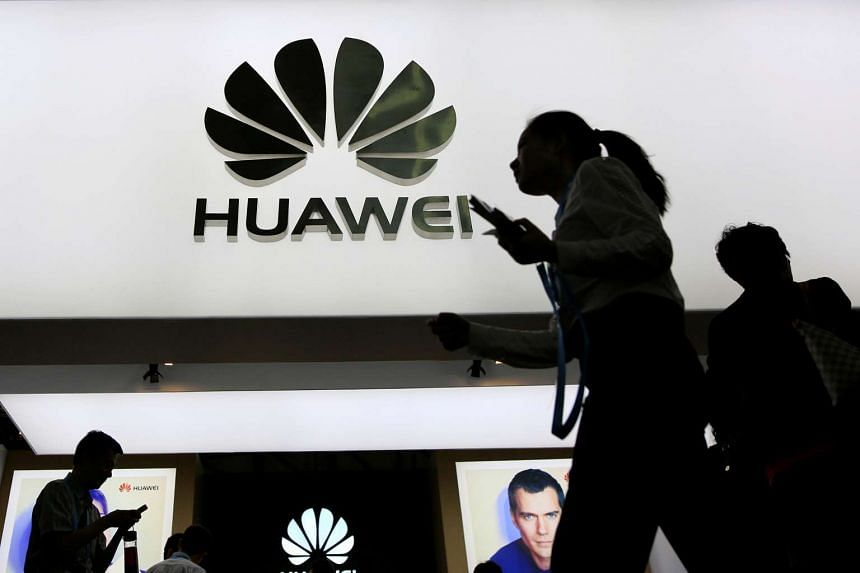 People walk past a Huawei sign board at CES Asia in Shanghai, China May 12, 2016.