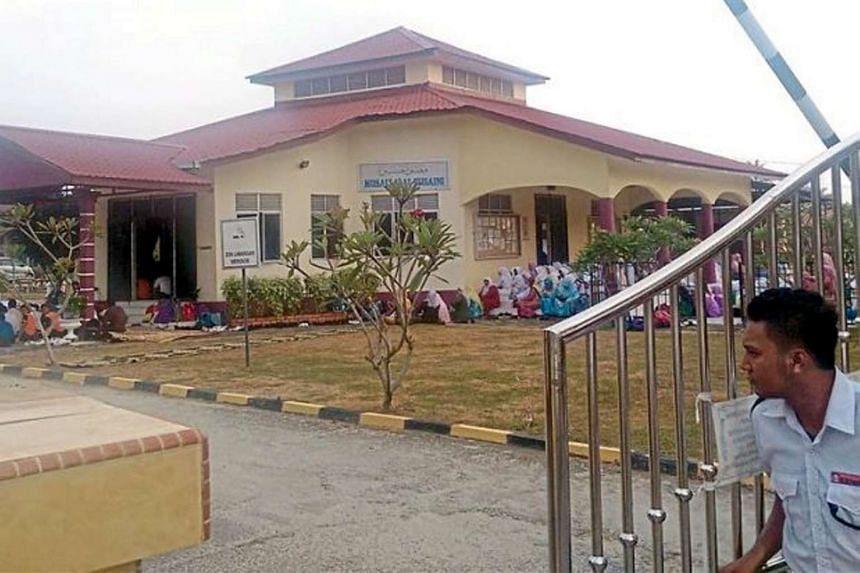 A security guard closing the gate of Sekolah Menengah Kebangsaan Kemumin in Kota Baru, Kelantan, Malaysia.