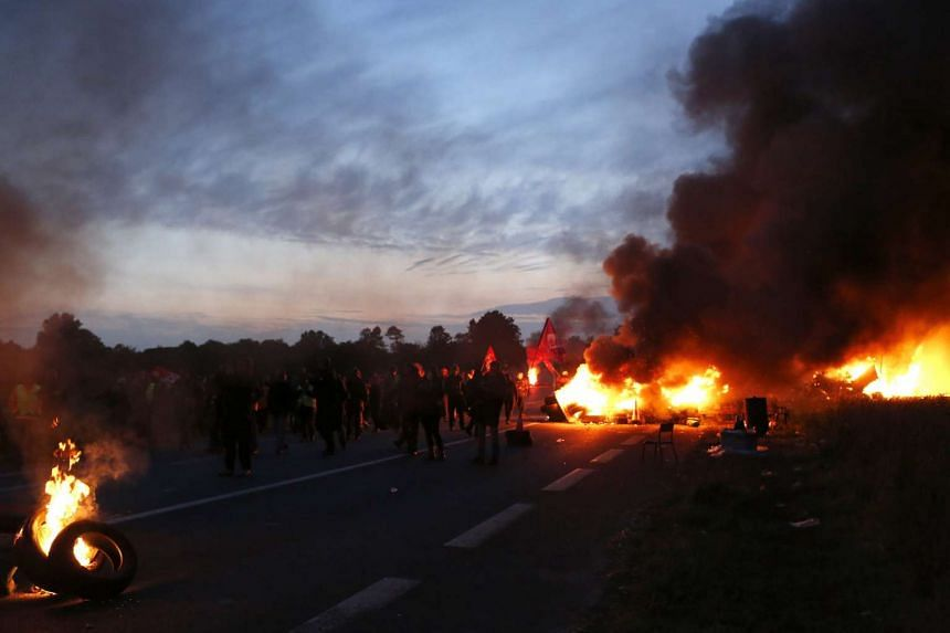 Trade unionists erect a burning barricade to block the entrance of a refinery before being dislodged by French police, in Douchy-les-Mines, France on May 25, 2016.