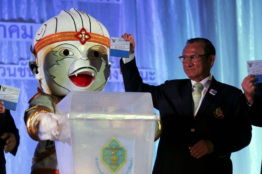 Thailand Election Commission chairman Supachai Somcharoen (right) casting an example ballot while standing next to commission's mascot, in Bangkok, Thailand, on May 25, 2016.