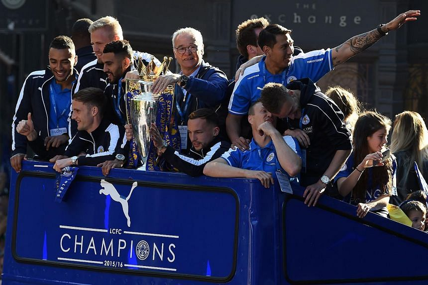 Claudio Ranieri (centre) holds the Premier league trophy as the Leicester City team take part in an open-top bus parade through Leicester.