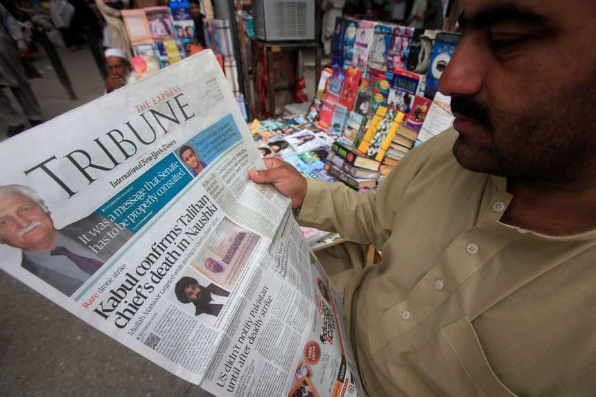 A man reads a newspaper containing news about Afghan Taleban leader Mullah Akhtar Mansour.