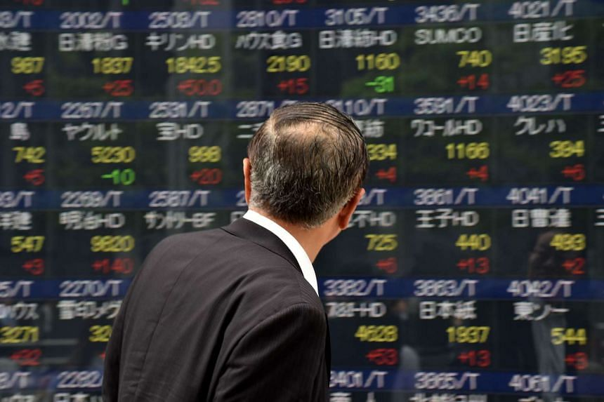 A pedestrian looks at a quotation board displaying the Nikkei key index from the Tokyo Stock Exchange in Tokyo on May 25.