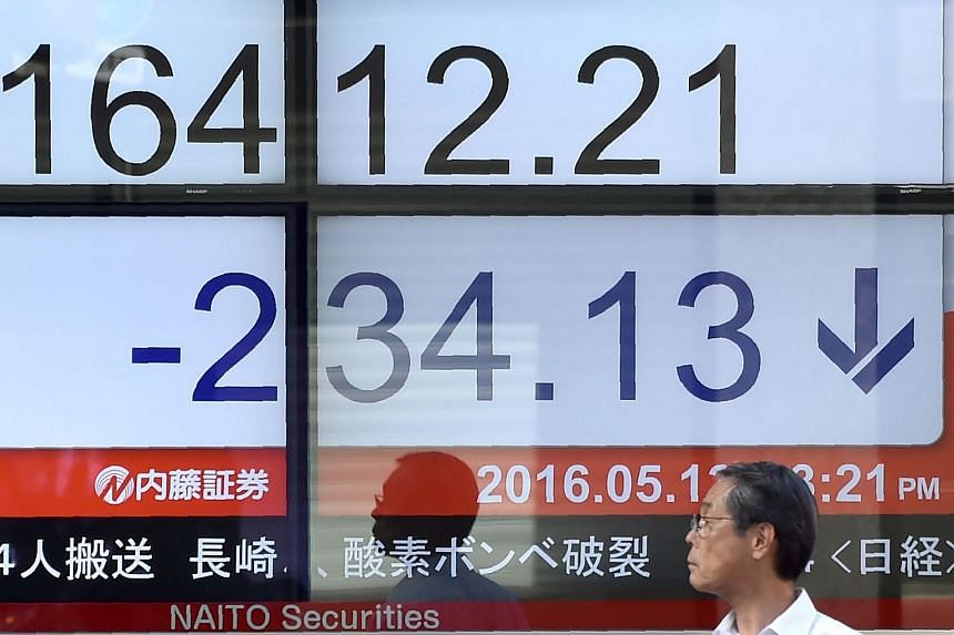 A pedestrian stands in front of a quotation board flashing the Nikkei key index from the Tokyo Stock Exchange in Tokyo on May 13.
