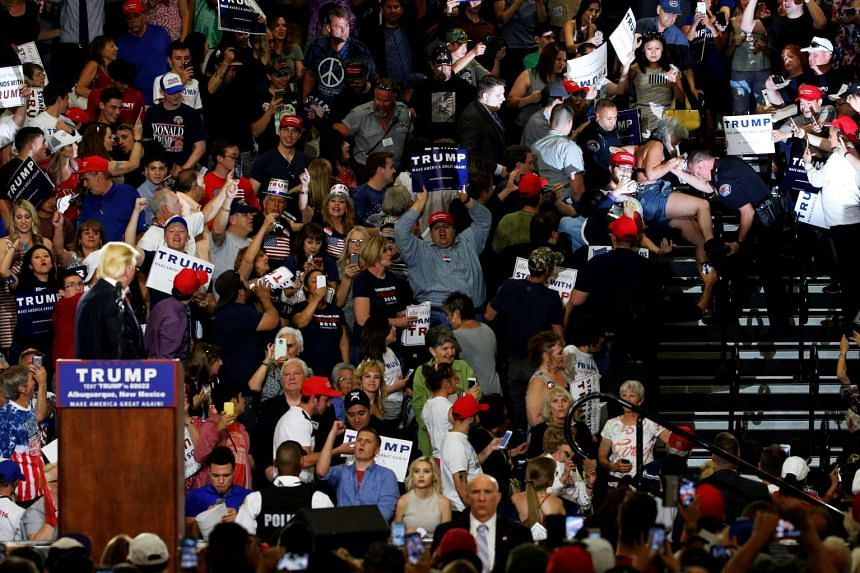 Republican US presidential candidate Donald Trump (bottom left) watches as police remove protester (right) as he holds a rally with supporters in Albuquerque, New Mexico, US on May 24.