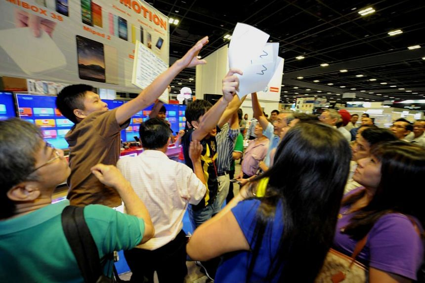 Visitors grabbing the limited vouchers which entitles them to a discount for the XiaoMi TV box.