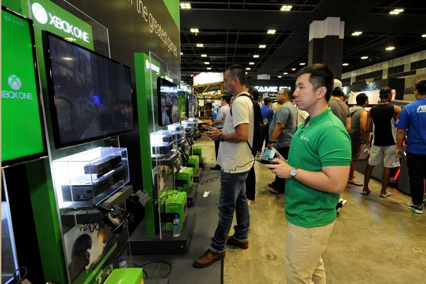 Visitors try out Xbox gaming consoles at the Consumer Electronics Exhibition.