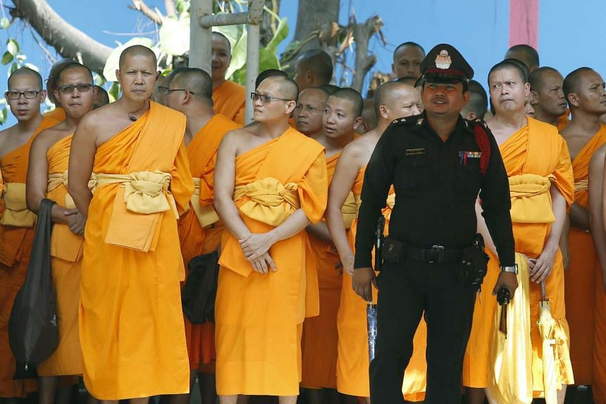 Thai Buddhist monks wait for Phra Dhammachayo to receive an arrest warrant, in front of the Khlongluang Provincial police station in Thailand, on May 26, 2016.
