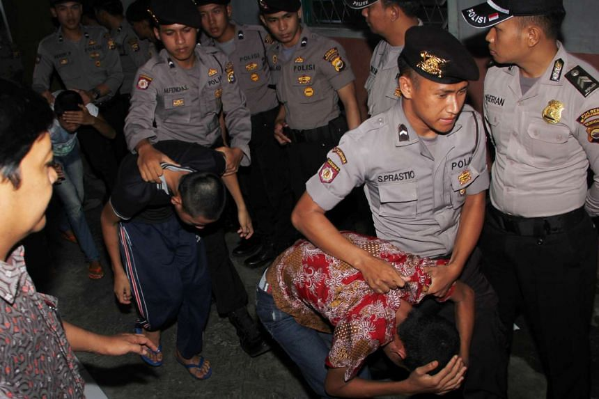 Indonesian policemen escort teenage suspects in the gang rape and murder of a 14-year-old girl, prior to their trial on May 10, 2016.