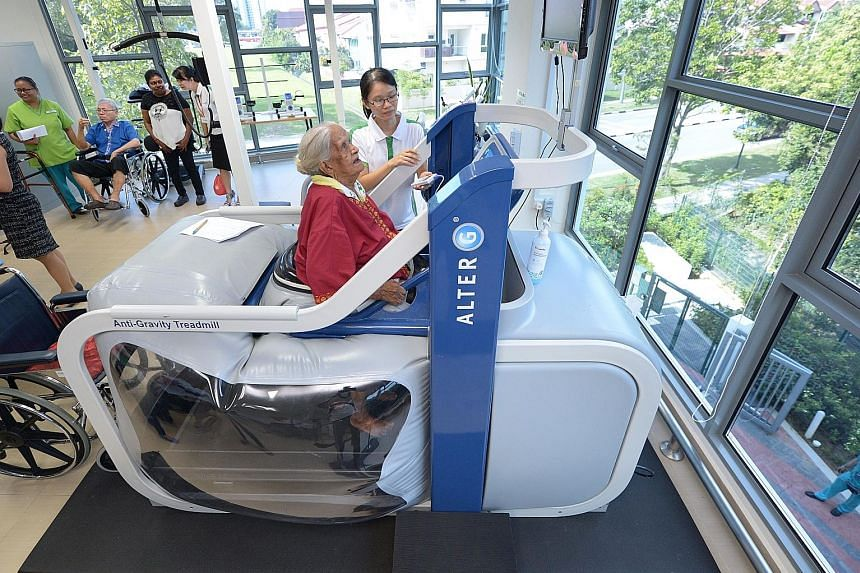 Madam Karumaya Kaiyammal, who is 101 years old, exercising on the anti-gravity treadmill machine under the supervision of physiotherapist Lee Pei Pei at the NTUC Health nursing home in Jurong West yesterday. Based on space technology that uses air pr