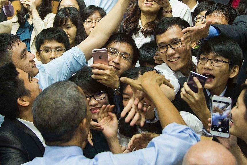 Mr Barack Obama (bottom left) greeting audience members after the Young South-east Asian Leaders Initiative town hall event in Ho Chi Minh City yesterday.