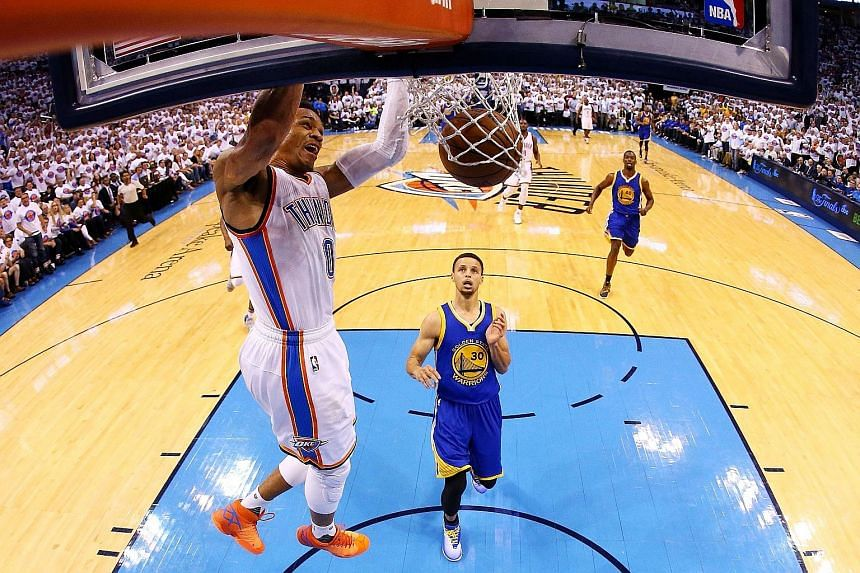 Oklahoma City's Russell Westbrook dunks as Stephen Curry (No. 30) of the Golden State Warriors looks on helplessly on Tuesday. The Thunder's 118-94 victory gave them a 3-1 lead in the Western Conference Finals.
