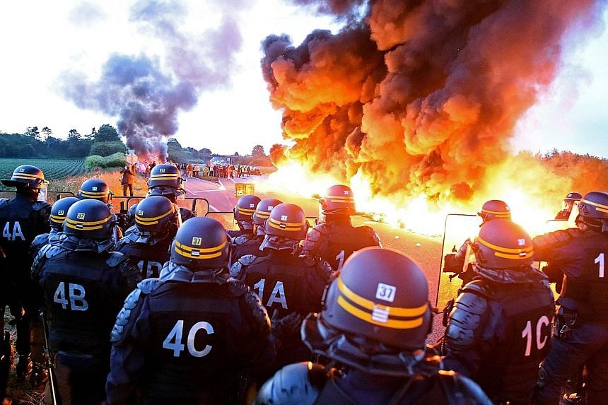 Riot police on guard behind a fire yesterday as refinery workers staged a blockade of the oil depot of Douchy-Les-Mines in northern France, to protest against the government's proposed labour reforms. Refinery workers stepped up strikes that threaten