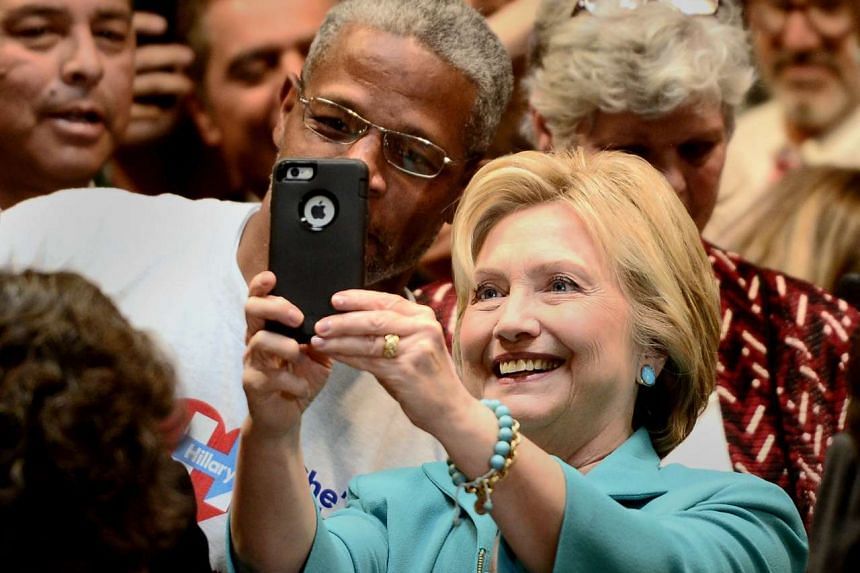Clinton (right) takes selfies with supporters at an event in California, May 24, 2016.