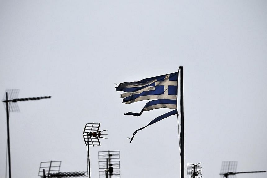 A frayed Greek national flag flutters among antennas atop a building in central Athens, Greece.