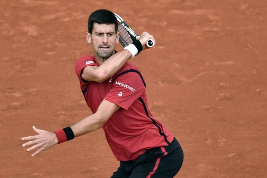 Novak Djokovic returns the ball to Taiwan's Lu Yen-Hsun in their men's first round match at the Roland Garros 2016 French Tennis Open, on May 24, 2016.