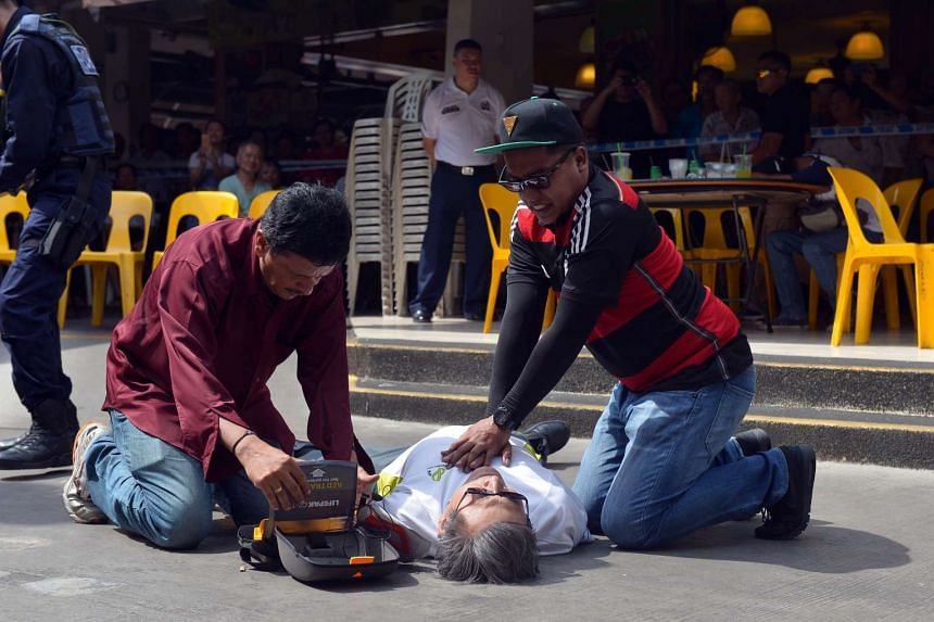 People conducting first aid on a victim during a staged terrorist attack at the Chong Pang EP Day on May 26, 2016.