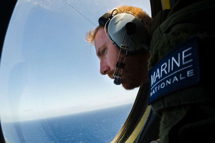 A French solider aboard an aircraft looking out a window during searches for debris from the crashed EgyptAir flight MS804 on May 22, 2016, over the Mediterranean Sea.