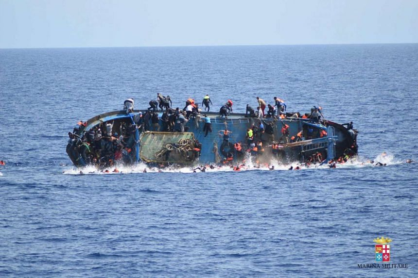 People jumping out of a boat right before it overturns in the Canal of Sicily off the Libyan coast, on May 25, 2016.