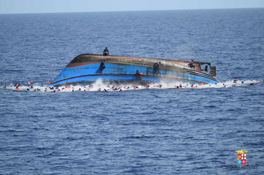 People jumping off with others in the waters around a capsized boat as it overturns in the Canal of Sicily off the Libyan coast, on May 25, 2016.