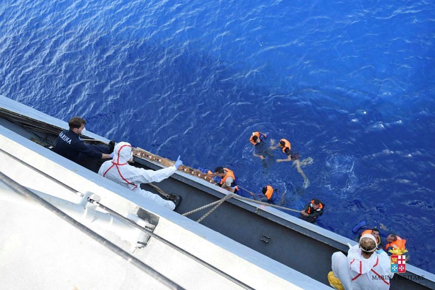 """Migrants from a capsized boat are rescued during a rescue operation by Italian navy ships """"Bettica"""" and """"Bergamini"""" off the coast of Libya, on May 25, 2016."""
