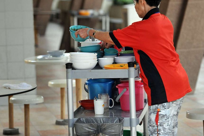 A cleaner clearing trays at a hawker centre.