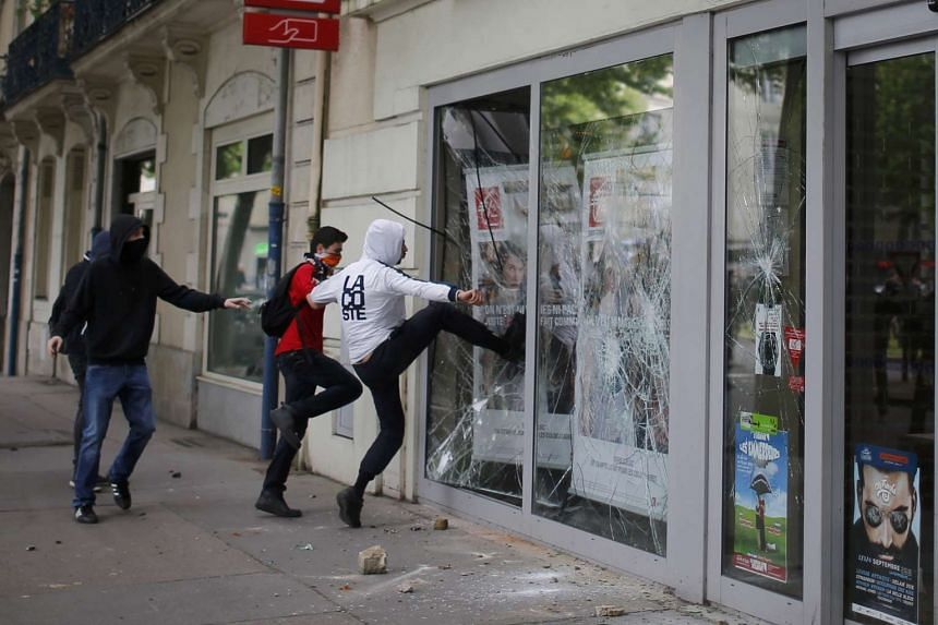 Youths break a bank window over labour reform plans in Nantes, France.