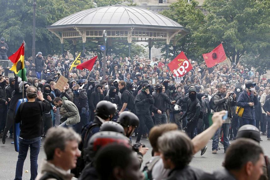 Masked youths with labour union flags are seen during clashes with French gendarmes and riot police in Paris.