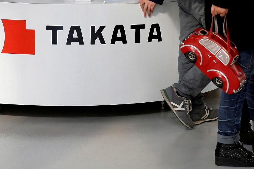 Visitors walk past a logo of Takata Corp on its display at a showroom for vehicles in Tokyo, Japan, Feb 5, 2016.