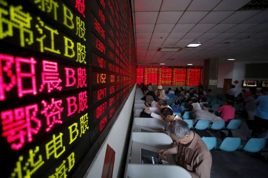Investors look at computer screens showing stock information at a brokerage house in Shanghai, on May 26, 2015.