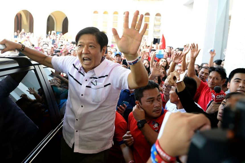 Ferdinand Marcos Jr (left) waves to supporters after attending a mass at the Redemptorist Church in Manila, on May 15, 2016.