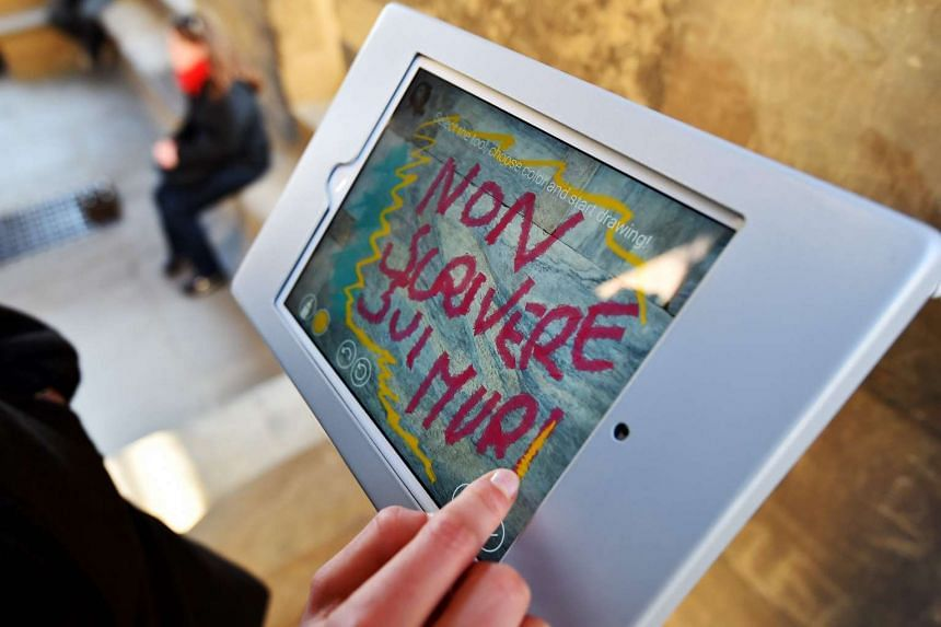 """A woman writes a digital graffiti reading """"Do not write on walls"""" on a tablet screen, on March 17, 2016, in Florence."""